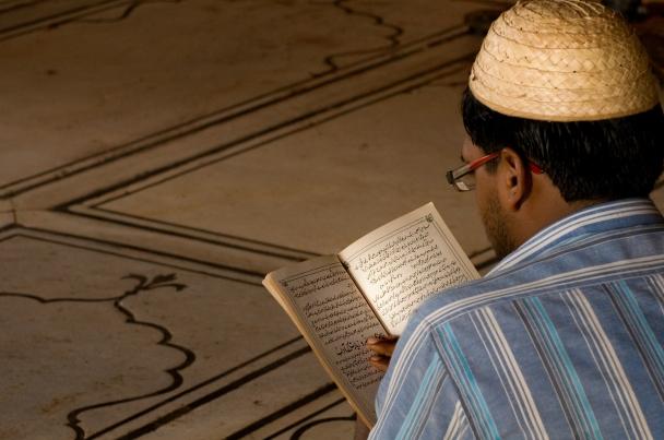 Giovane musulmano legge il corano nella grande moschea del venerdì di Delhi